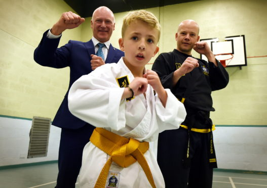 Alex Crichton practices his Choi Kwang-Do with instructor Dave Skinner and Public Health Minister Joe FitzPatrick