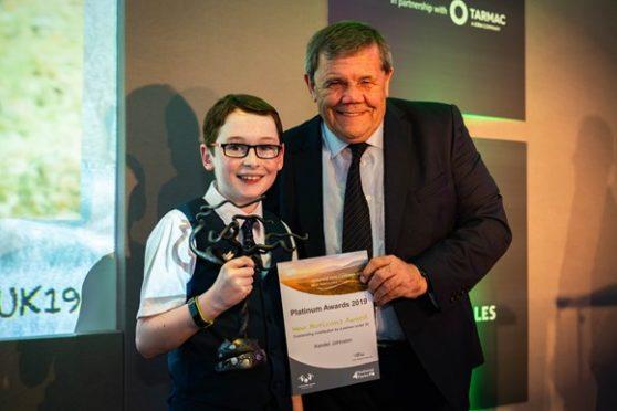 Xander Johnston receiving his award from carl Lis