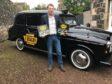 Derek Caroll holding the original Taxi board game.