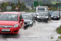 Traffic, including an ambulance has to make its way through deep floodwater on the A9 at Inverness on Saturday morning during torrential rain. Picture and video by Sandy McCook.
