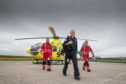 Pilot Shaun Rose and paramedics Darren O'Brien (L) and Matt Allen alongside the SCAA Helicopter