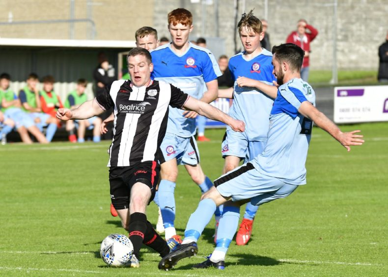 Wick's Davie Allan weaves past the Turriff defence