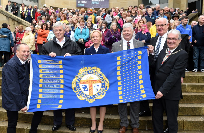 Convener of the Glasgow local Mod Committee, DI Brown (left) hands over the Mod flag to Inverness ahead of next year's Mod in the Highland capital. (L-R) Allan Campbell, Chairman of An Comunn Gaidhealach, Donna Manson, Chief Executive of Highland Council, Alisdair Barnett, Chairman of the local organising committee for next years Royal National Mod in Inverness, Alister Mackinnon of Highland Council and Inverness Deputy Provost Graham Ross. Picture by Sandy McCook