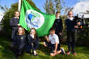 MONQUHITTER PRIMARY SCHOOL ECO COMMITTEE PUPILS (L TO R) KELSEY SUTHERLAND, EMMA WATSON, CONNIE COWIE, ARCHIE CLARK AND CONNOR COWIE RAISE THE GREEN FLAG TO THE SOUNDS OF PIPER AIMEE HOWITT.