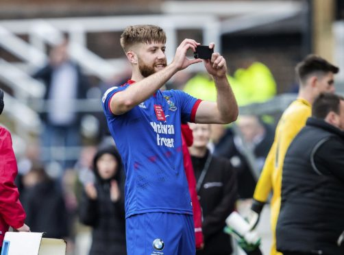Shaun Rooney takes photos with the Caley Thistle fans at full-time.