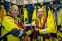Davie Weir receives his Boat's Officer's hat from Lifeboat operations manager Jurgen Wahle