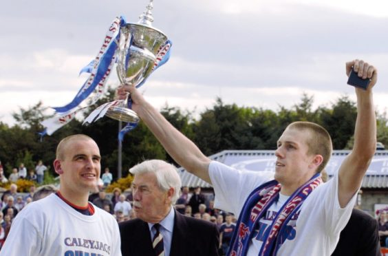 Steven Hislop holds aloft the 2004 First Division title.
