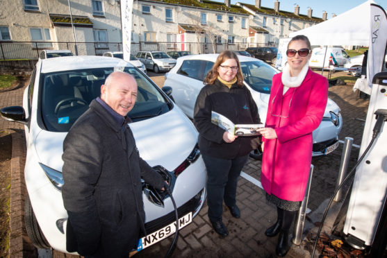 Jane McWhirr, pictured centre, Osprey Housing Group's Sustainability Officer shows Osprey tenants David and Melanie Smith how the car club membership works.
