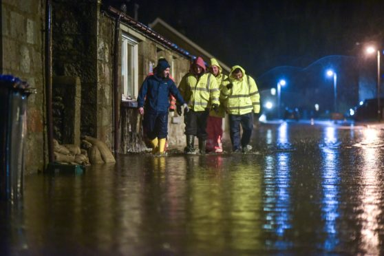 Men search homes in the Port Elphinstone area of Inverurie, Aberdeenshire as they begin to experience flooding after the River Don burst its banks on January 07 2016