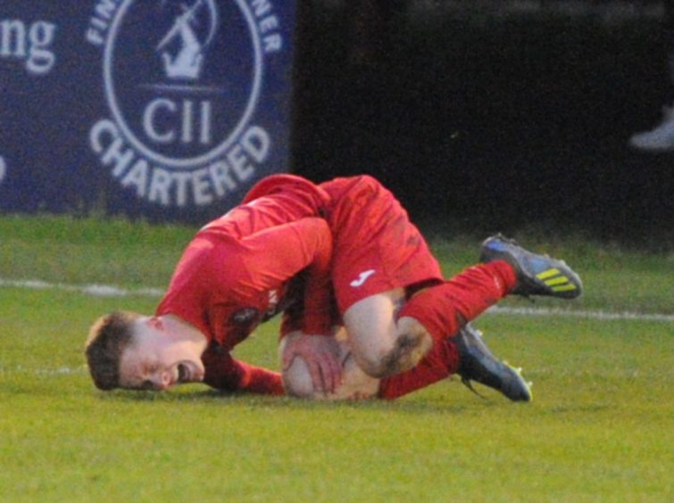 Brora 10 Andrew Macrae is fouled by Buckie 8 Jay Cheyne resulting in a sending off. Picture by JASON HEDGES