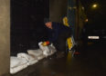 Landlord Frank Ralph is pictured placing sandbags at one of his properties.  Pictures by JASON HEDGES
