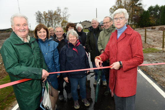 Former Highland Councillor Isobel McCallum cuts the ribbon to officially open the new junction. Also in the photograph are local campaigners who fought for the improvements. Picture by Sandy McCook