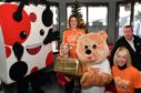 THE DEVERON HOMESTART GIVING TREE WAS LAUNCHED AT THE SPOTTY BAG SHOP IN BANFF WITH SHOP MASCOT SPENCER HANDING OVER THE FIRST PARCEL TO THE HOMESTART BEAR.LOOKING ON ARE (L TO R) TRACY FLEMING AND DAUGHTER ELLA, SONIA PIRIE AND SHOP OWNER DES CHEYNE.