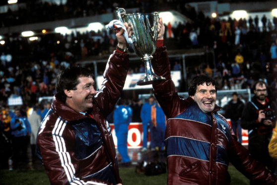 Aberdeen manager Alex Ferguson (left) and assistant Archie Knox celebrate with the trophy in 1983