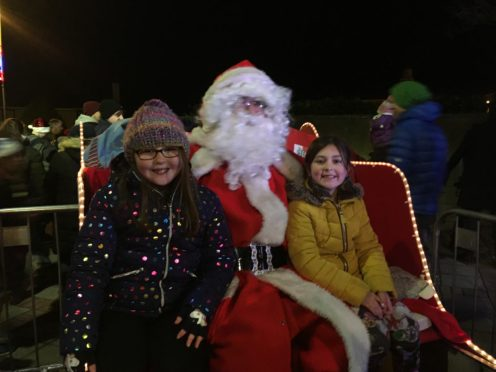 Emilee Hastie (left) and Jill Sinclair had the honour of switching on Nairn's Christmas lights with Santa.