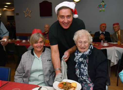 PETERHEAD FC MANAGER JIM MCINALLY SERVES CHRISTMAS DINNER TO  MORAG MCBAIN (L) AND JENNY RITCHIE AT THE CLUBS ANNUAL LUNCH FOR LONELY PEOPLE.