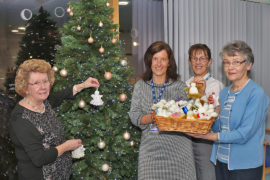Busy Hands group representatives Mary Cameron (left) and Roseanne Youngson (right) visited Chalmers Hospital, Banff, with a basket full of 50 angels which were accepted by Brenda Smart (centre left), area support manager, and Carlynn McLeod, clerical officer
